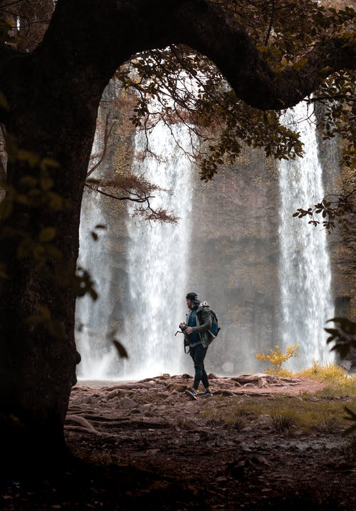 Man Stands in Front of Falls in Fforest