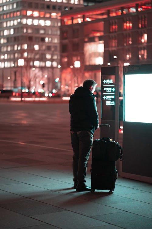 Man Standing Beside Black Luggage on Street