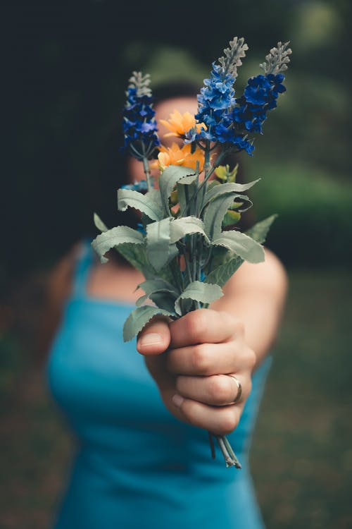 Selective Focus Photography of Woman Holding Blue Petaled Flower