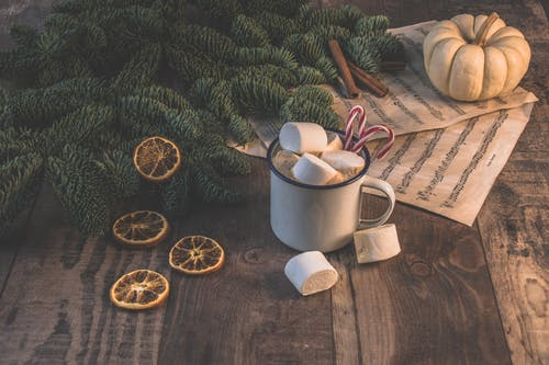 White Ceramic Mug With Coffee and Marshmallows Near Pinetree