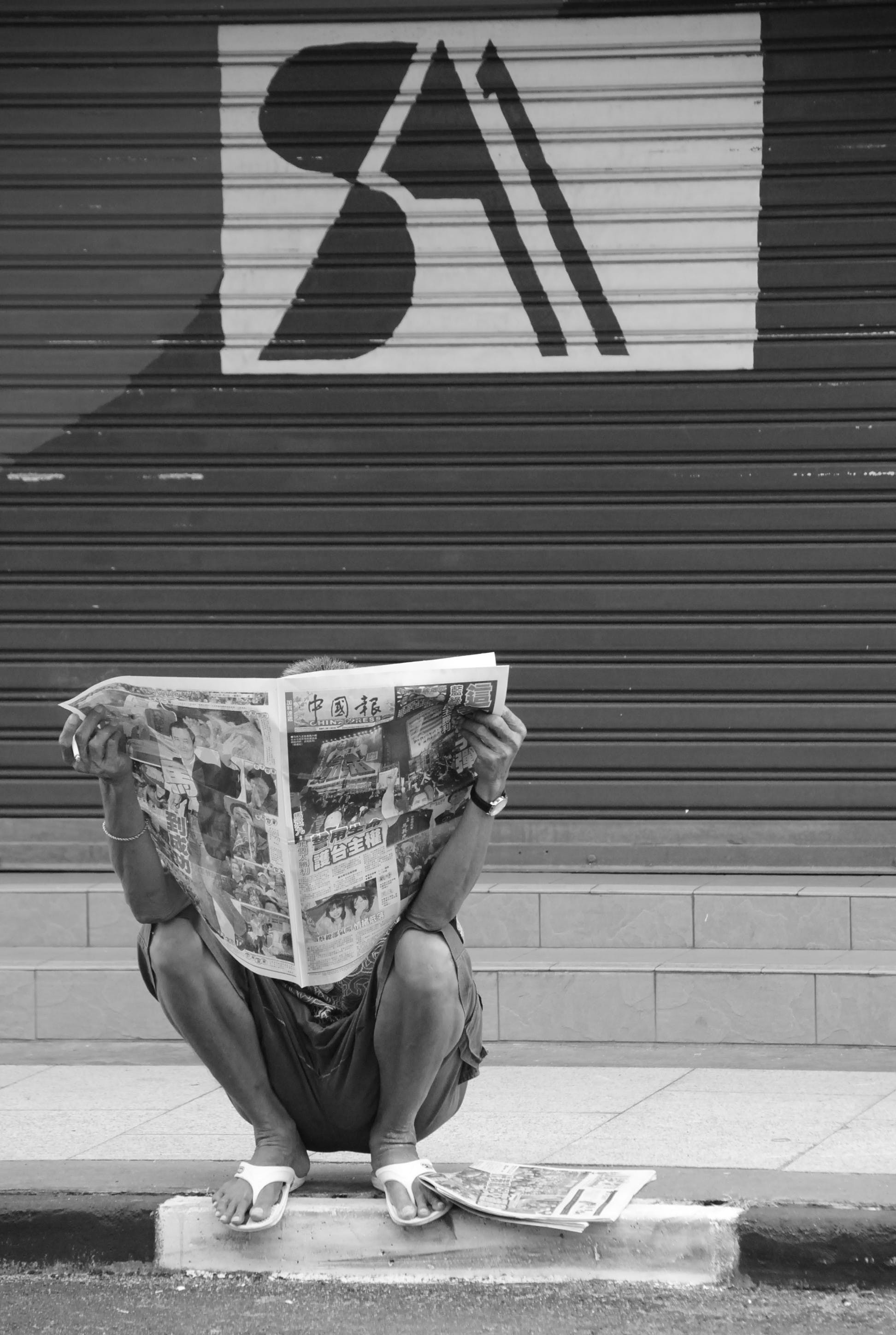 Person Sitting on Side Walk Reading Newspaper
