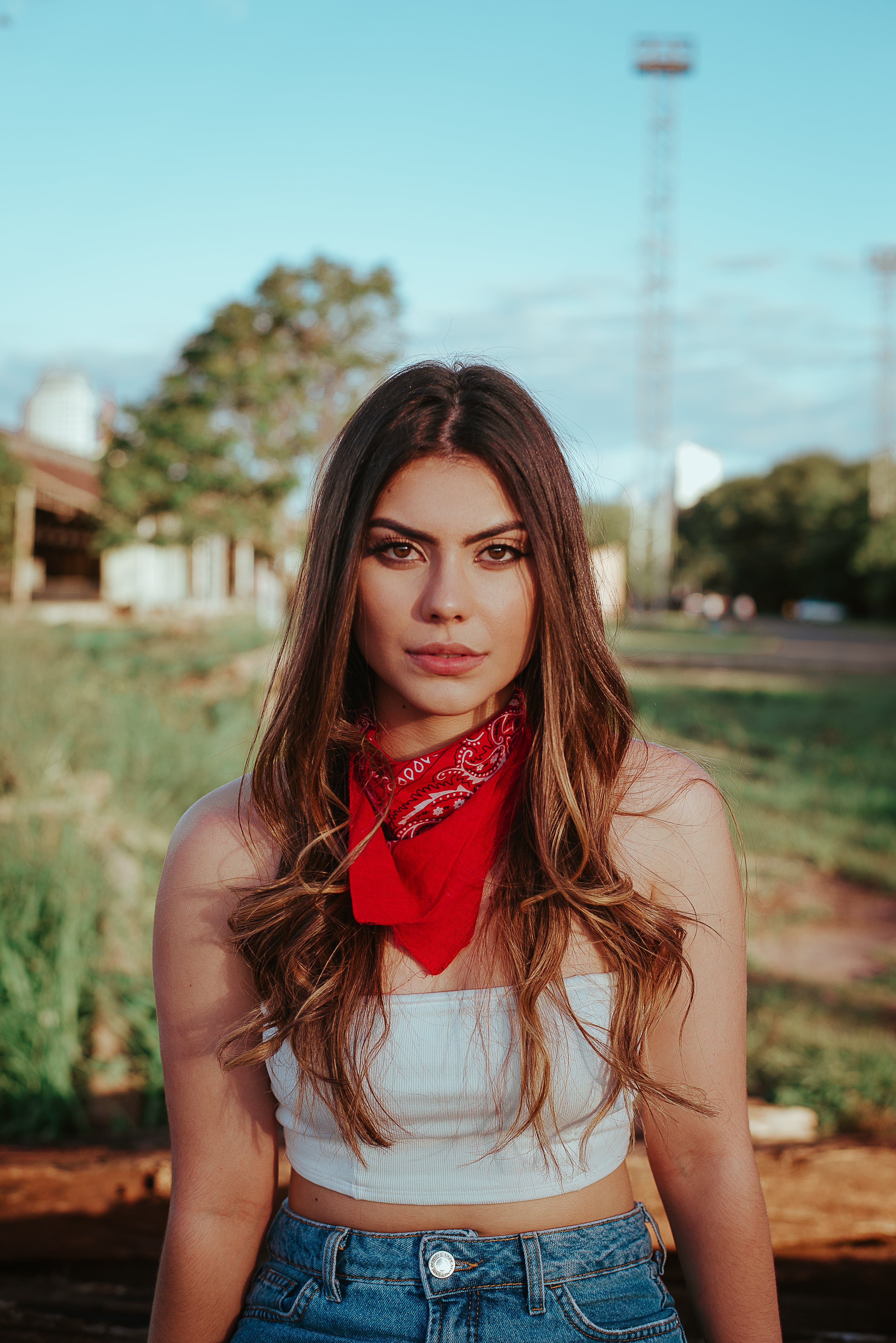 Woman Wearing White Crop Top, Blue Denim Bottoms and Red Bandana
