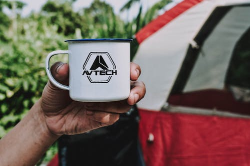 Person Holding White Avtech Cup