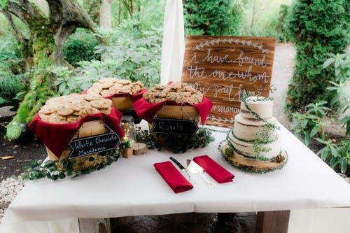 Free stock photo of beach wedding, carved wood, dessert table, evergreen