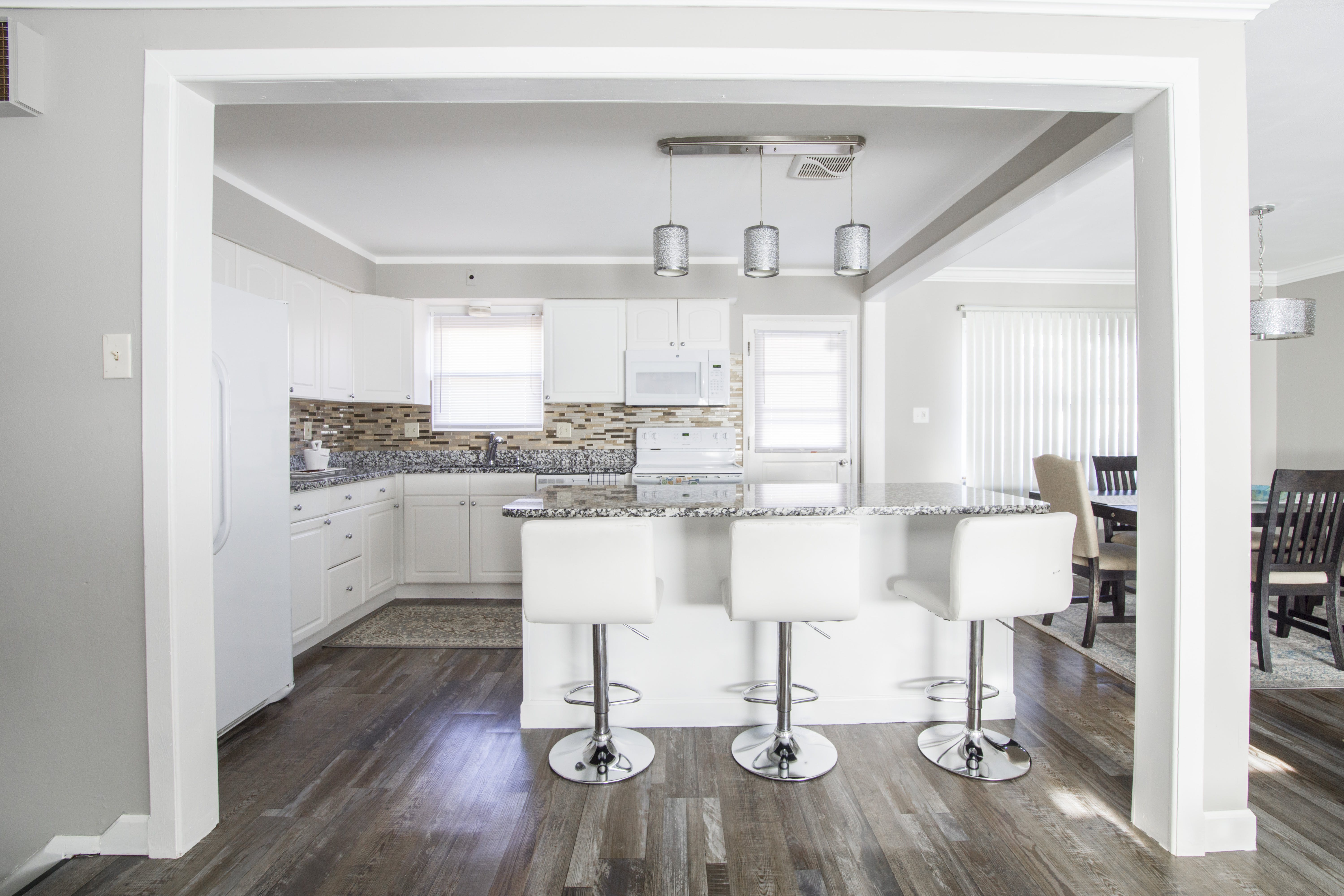Three White Barstools in Front of Kitchen Island