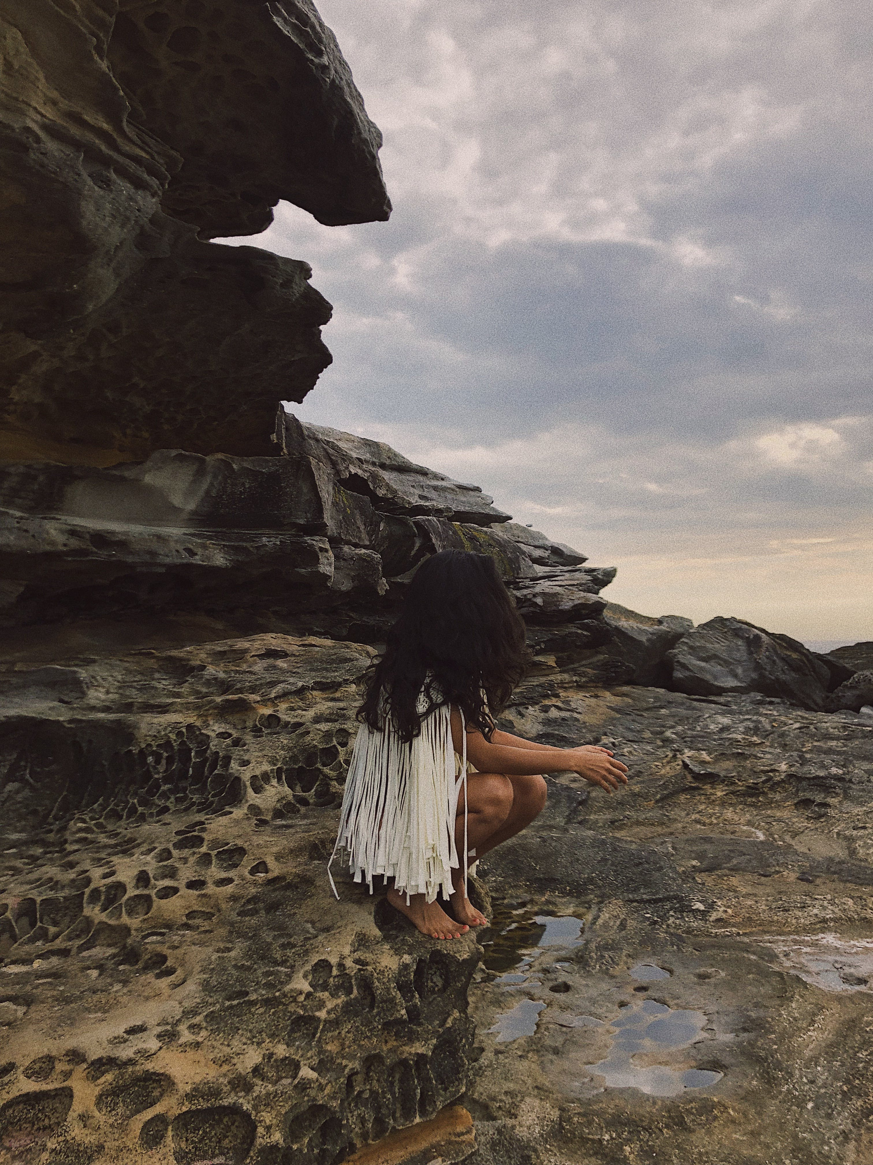 Selective Focus Photography of Woman Sitting on Rock Formation