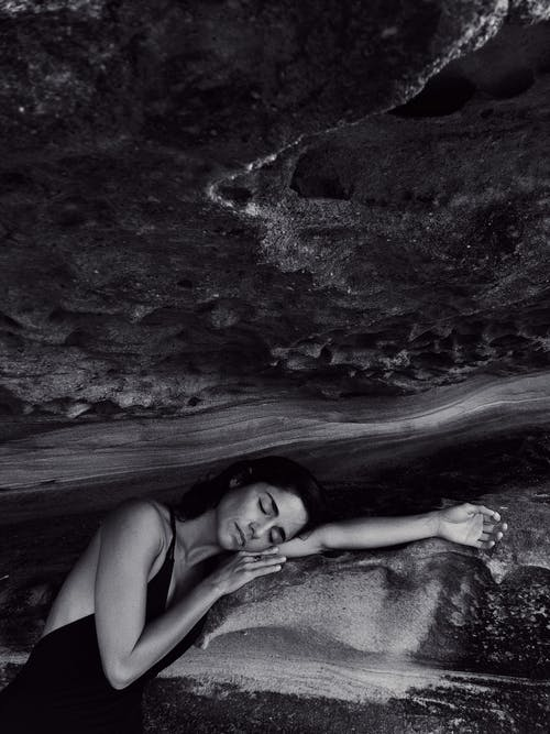 Grayscale Photography of Woman Leaning on Rock