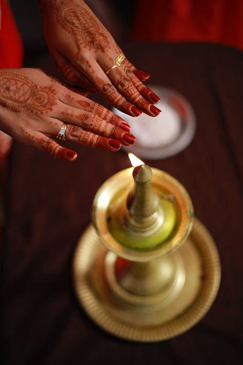 From above of anonymous woman holding hands with mehendi paintings above Nilavilakku lamp with burning flame