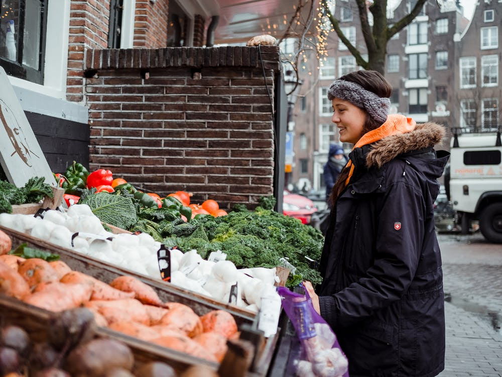 Woman Standing in Front of Vegetable Stall