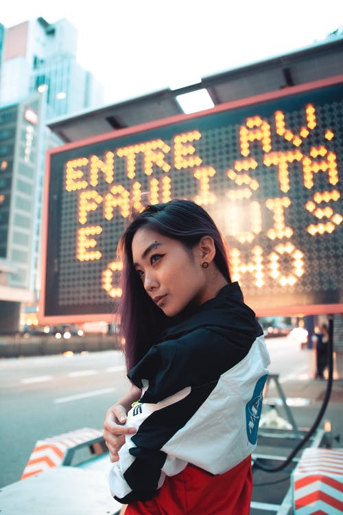 Selective Focus Photography of Woman Wearing Jacket Near Led Signage