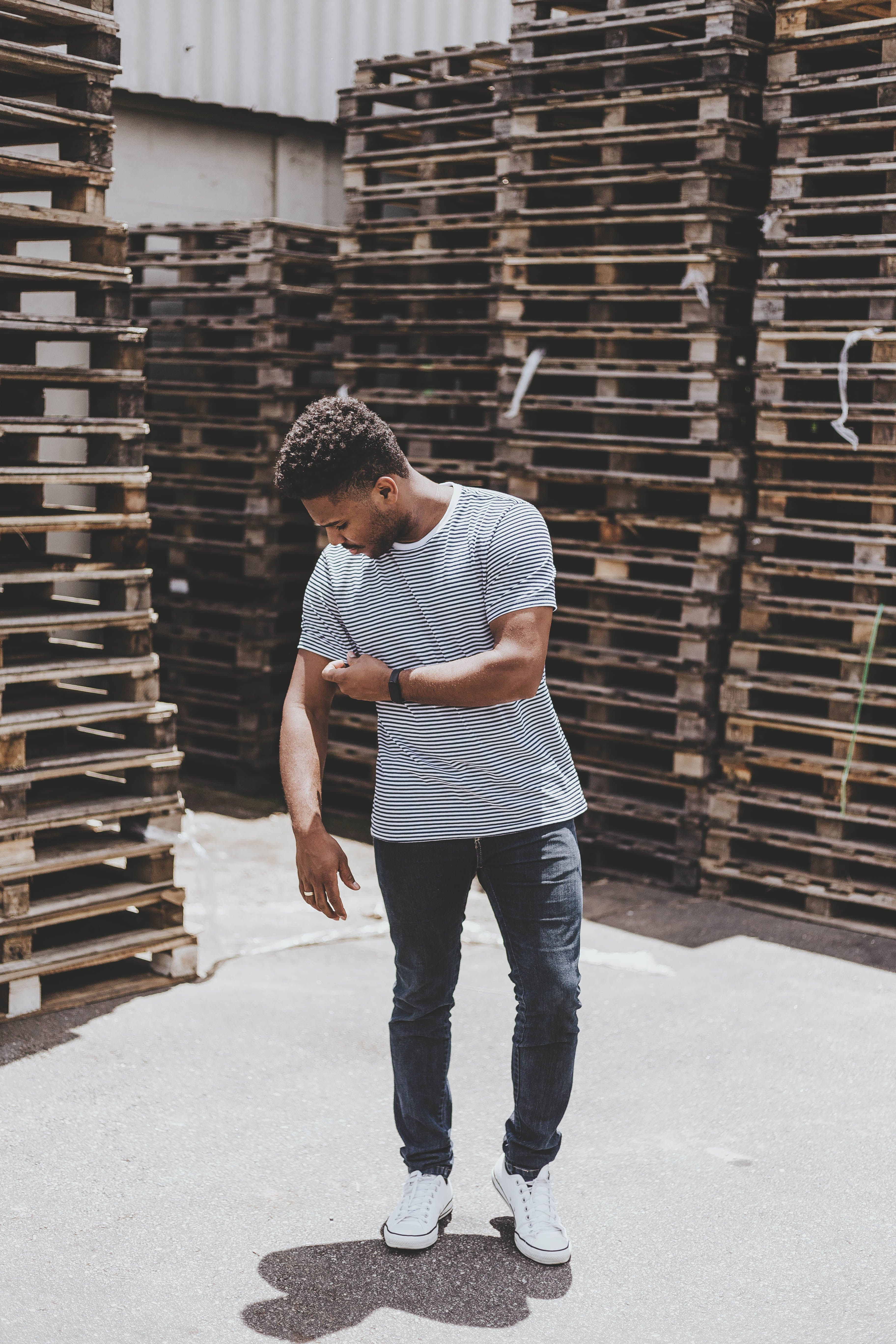 Man Standing Near Stack of Pallets