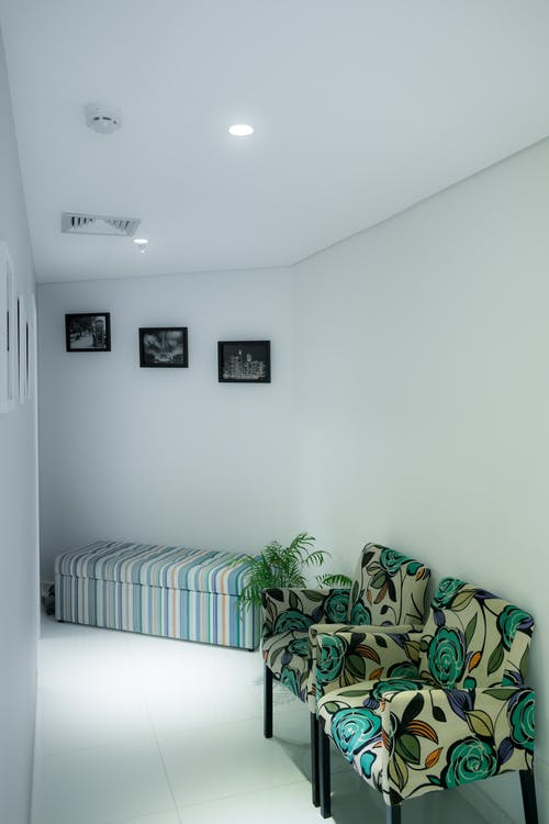 Two White and Green Floral Padded Sofa Chairs Next to Wall in Room