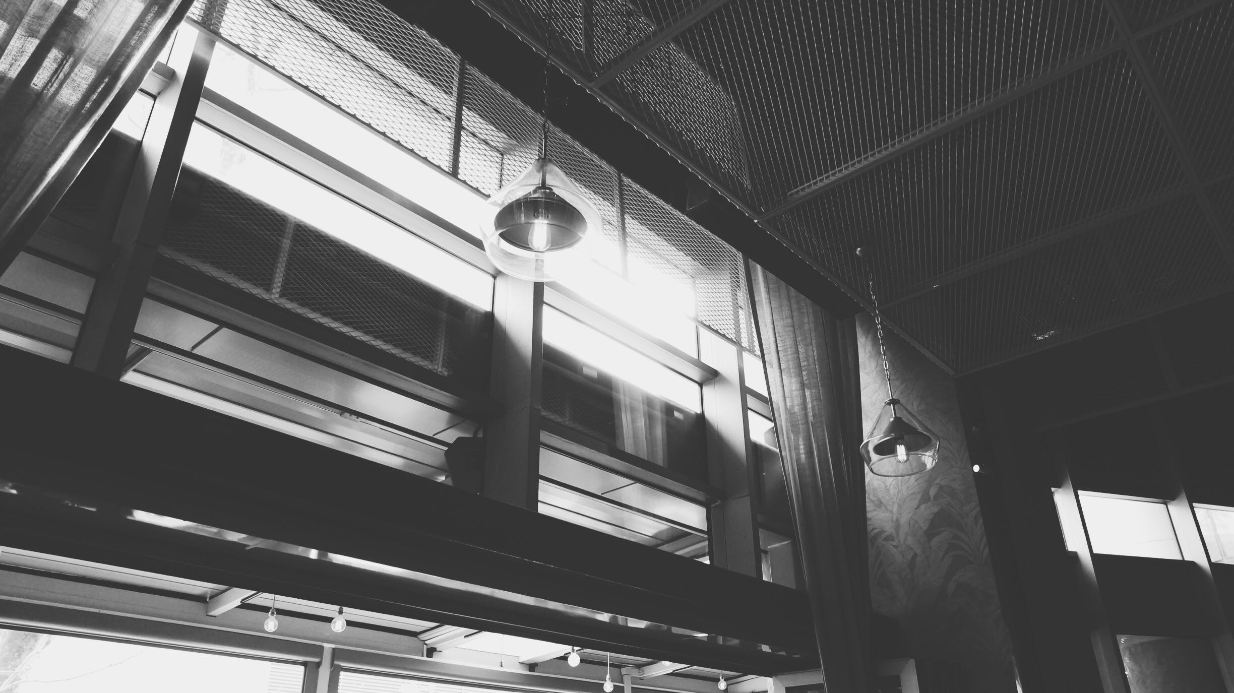 Grayscale Photo of Hanged Ceiling Lamp Inside the Building