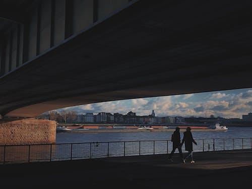 Two Person Walking Under Bridge