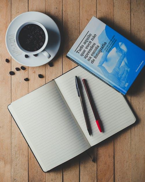 Free stock photo of cup, notebook, pen, raisins