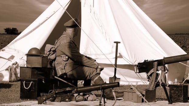 Sepia Photo of Man in Military Uniform Sitting Near Guns and White Gazebo