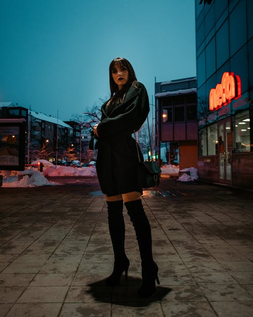 Woman Standing on Pathway Near Buildings