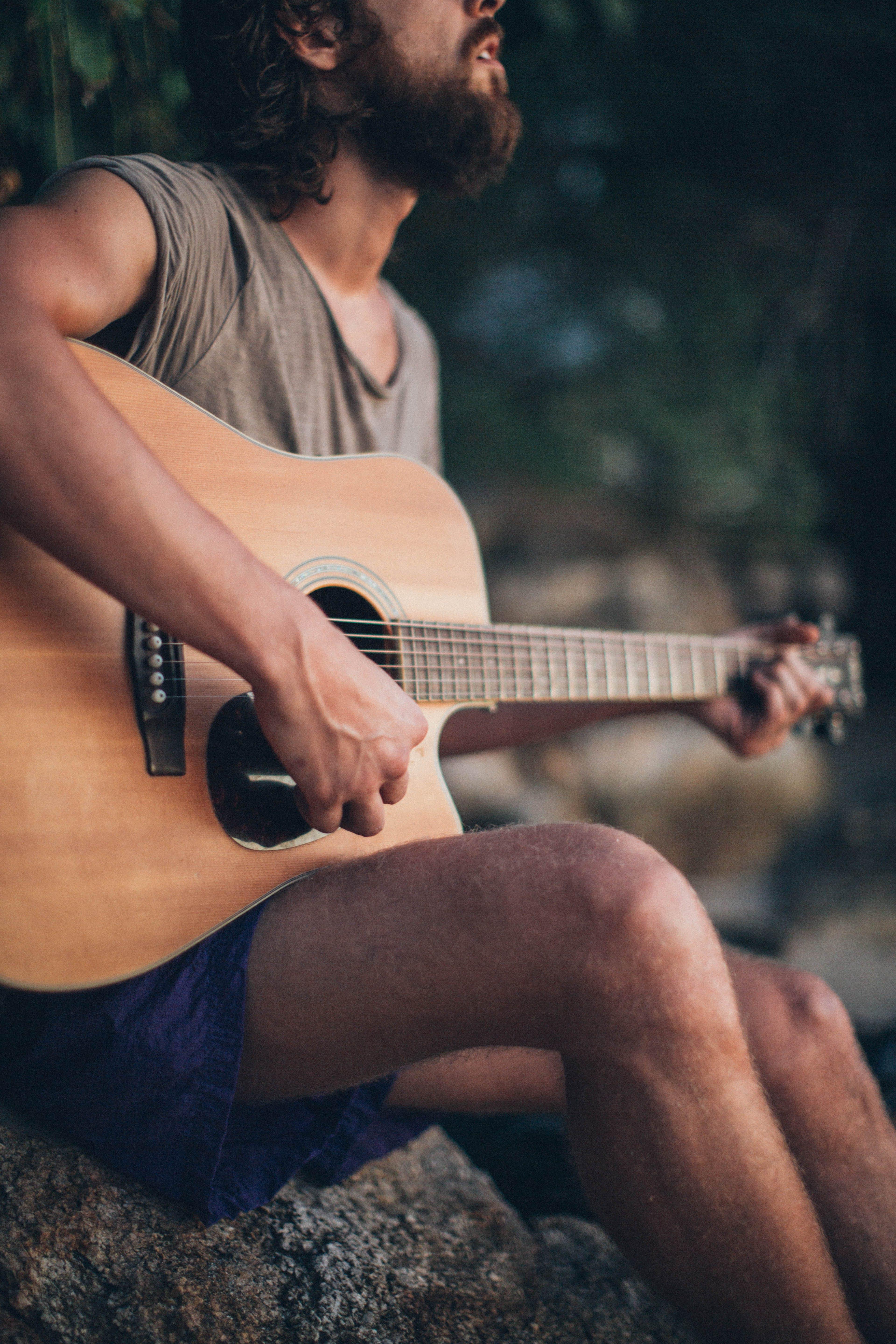 Man Sitting on Rock Playing Guitar