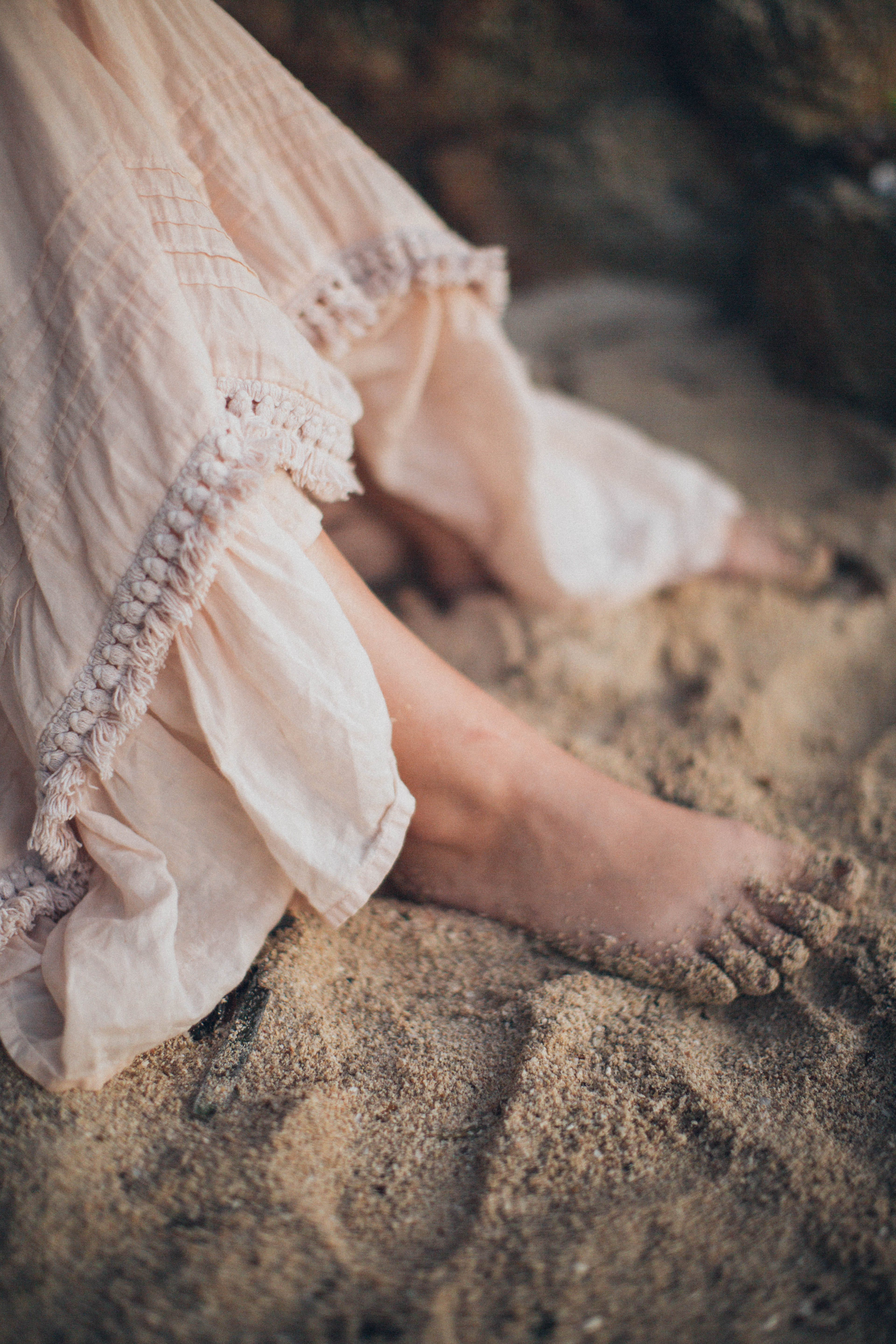Woman Wearing White Dress Stepping on Sand Barefooted