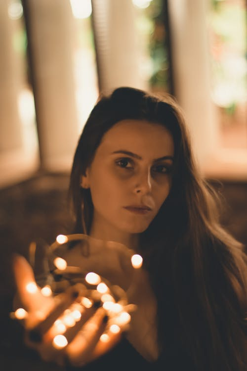Woman Holding String Light Indoors