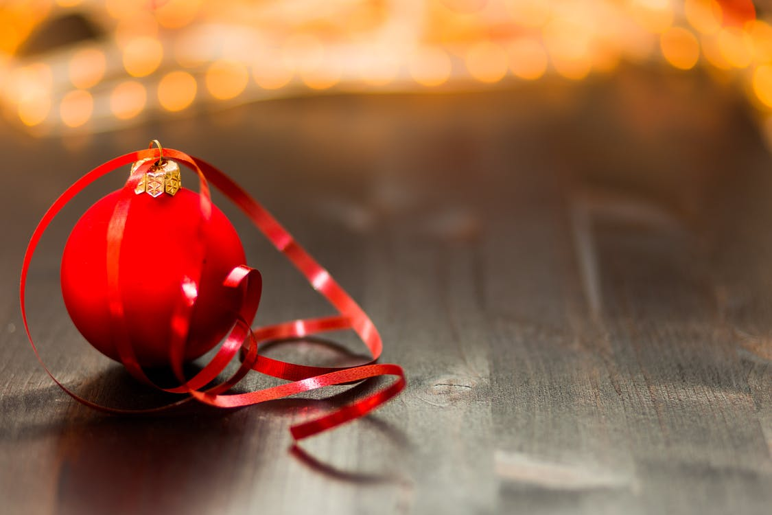 Red Christmas Bauble With Red Ribbon on Wooden Surface in Close Up Photography