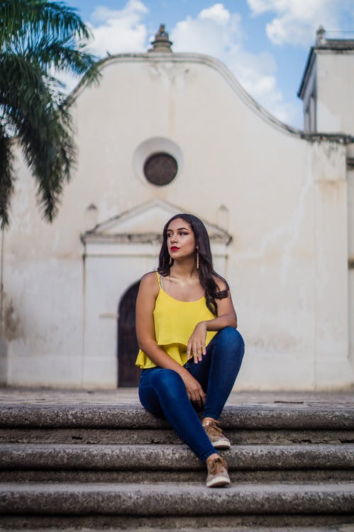 Photo of Woman in Yellow Sleeveless Top and Blue Jeans Sits on Staircase with White Building in the Background