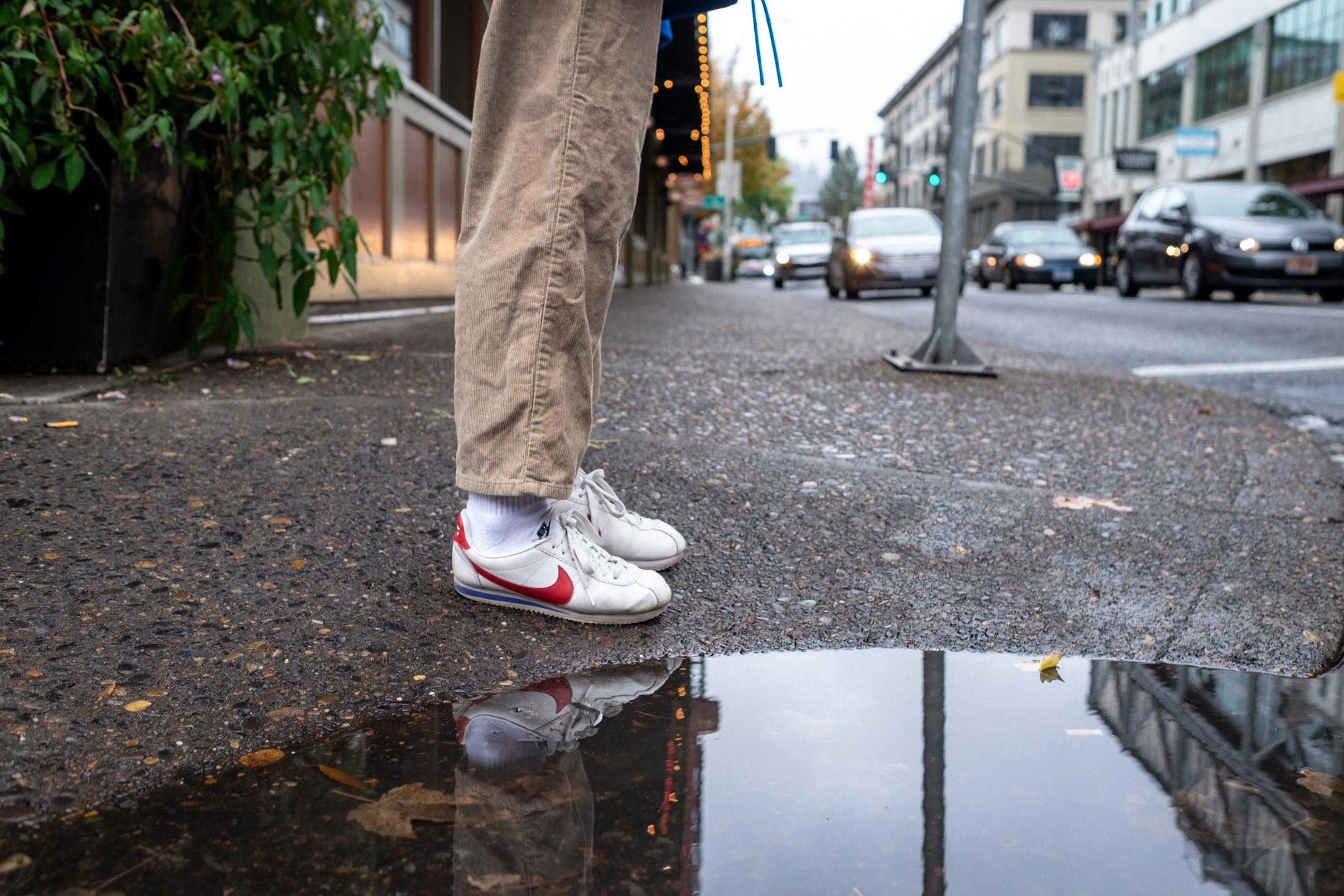 Photo of Person Wearing White and Red Nike Low-top Sneakers Standing Next to a Puddle