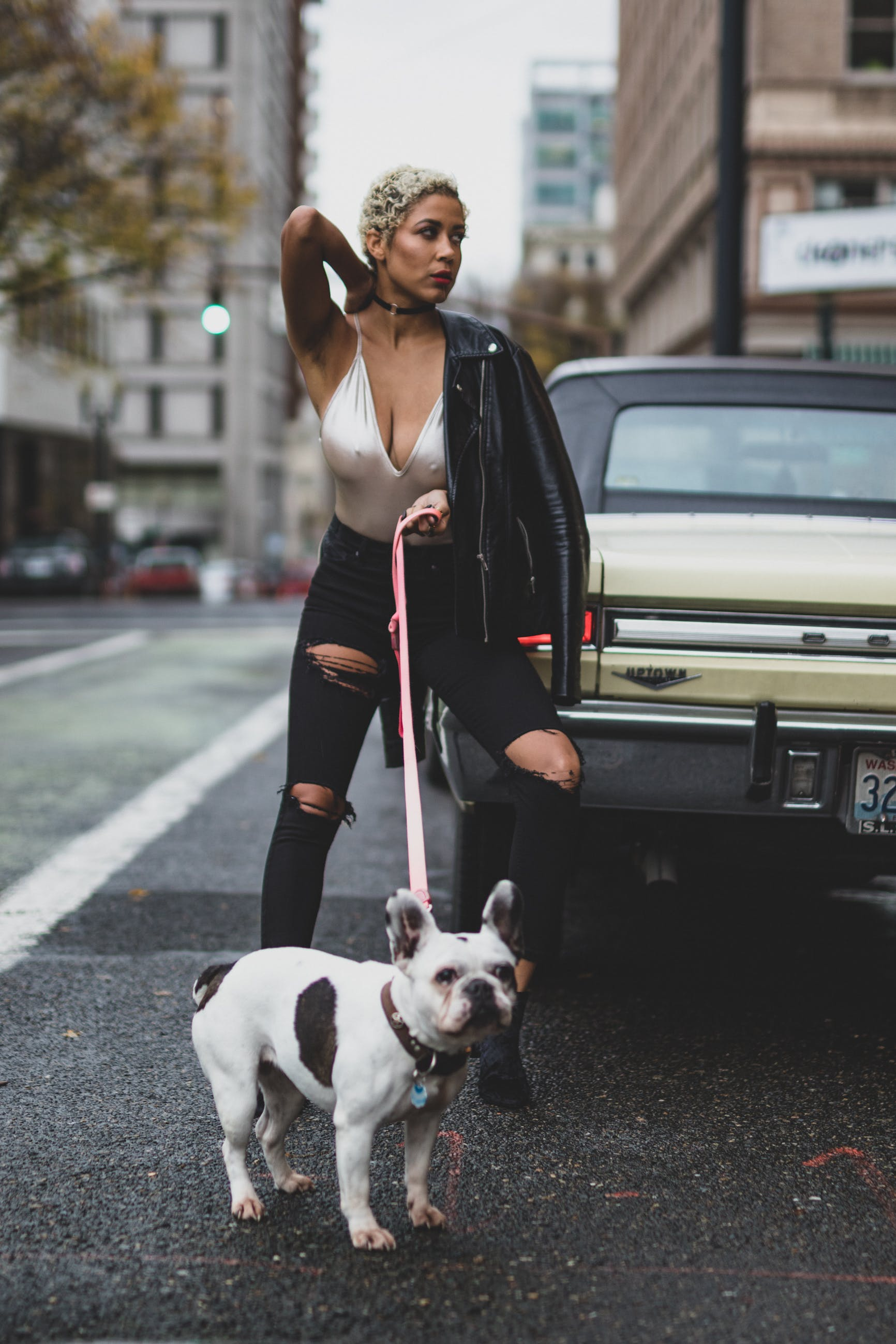 Woman in White Top and Black Leather Jacket Holding Dog With Leash