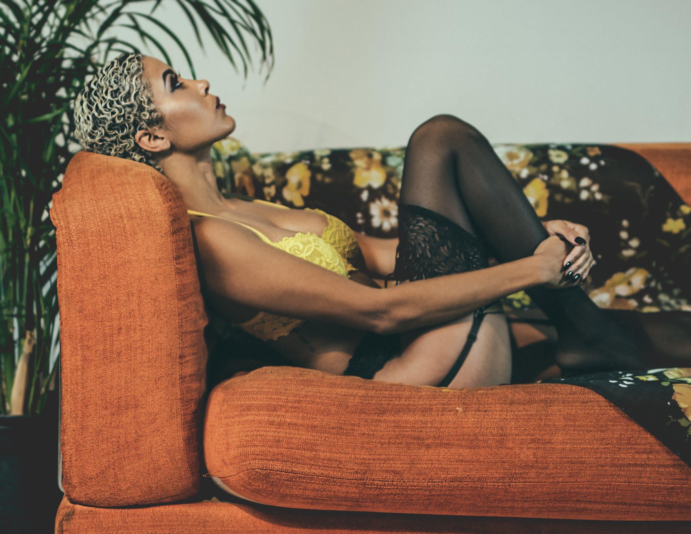 Woman Wearing Yellow Brassiere Sitting on Sofa