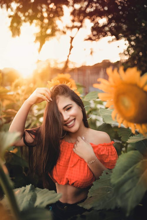 Woman Wearing Crop Top Surrounded by Sunflowers