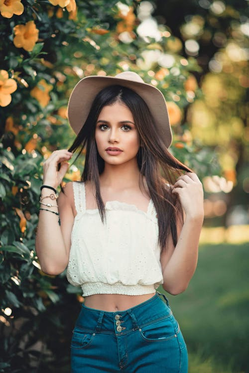 Woman in White Crop Top Standing Beside Plant