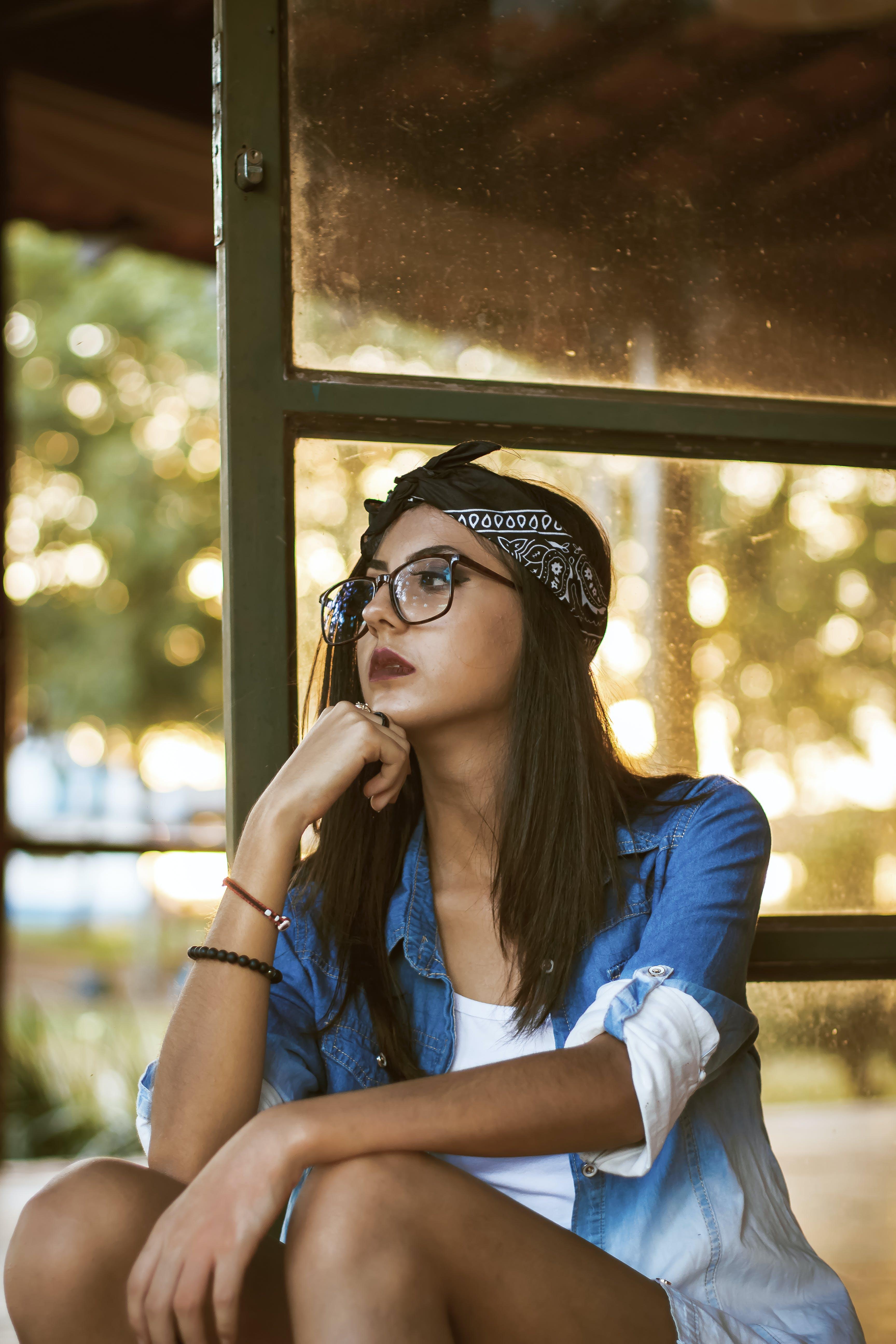 Woman Sitting Beside Glass Door
