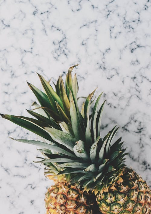Photo of Two Yellow Pineapples on Marble Surface