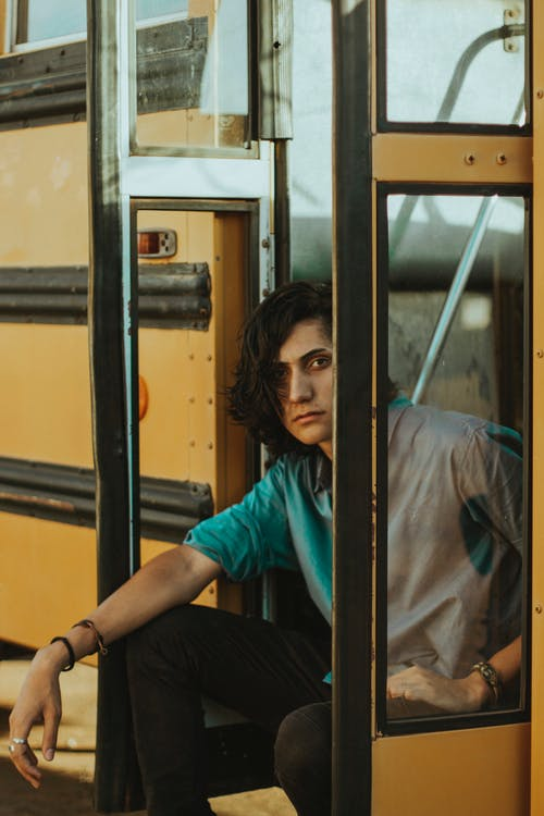 Man Sitting on Doorway of School Bus