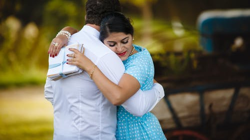 Ethnic couple in summer clothes hugging in green garden