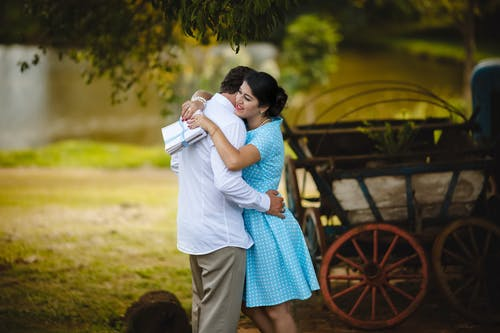 Cheerful ethnic lady in summer dress with stack of letters in hand tenderly embracing faceless boyfriend after long separation standing in green rural backyard