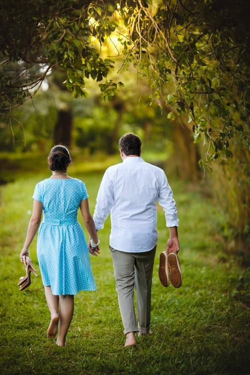 Back view of unrecognizable man and woman in love strolling barefoot and holding hands in quiet green park in summer
