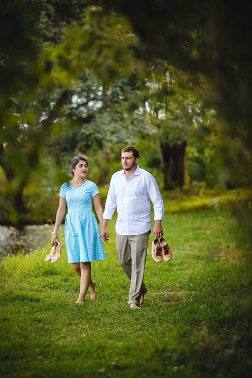 Young multiracial barefoot boyfriend and girlfriend holding hands and carrying shoes while walking in quiet summer park