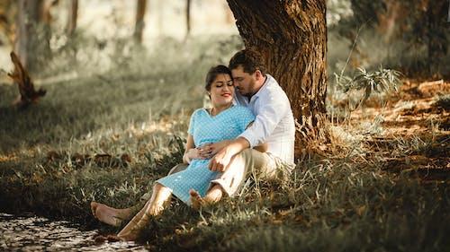 Couple in love cuddling under tree in park