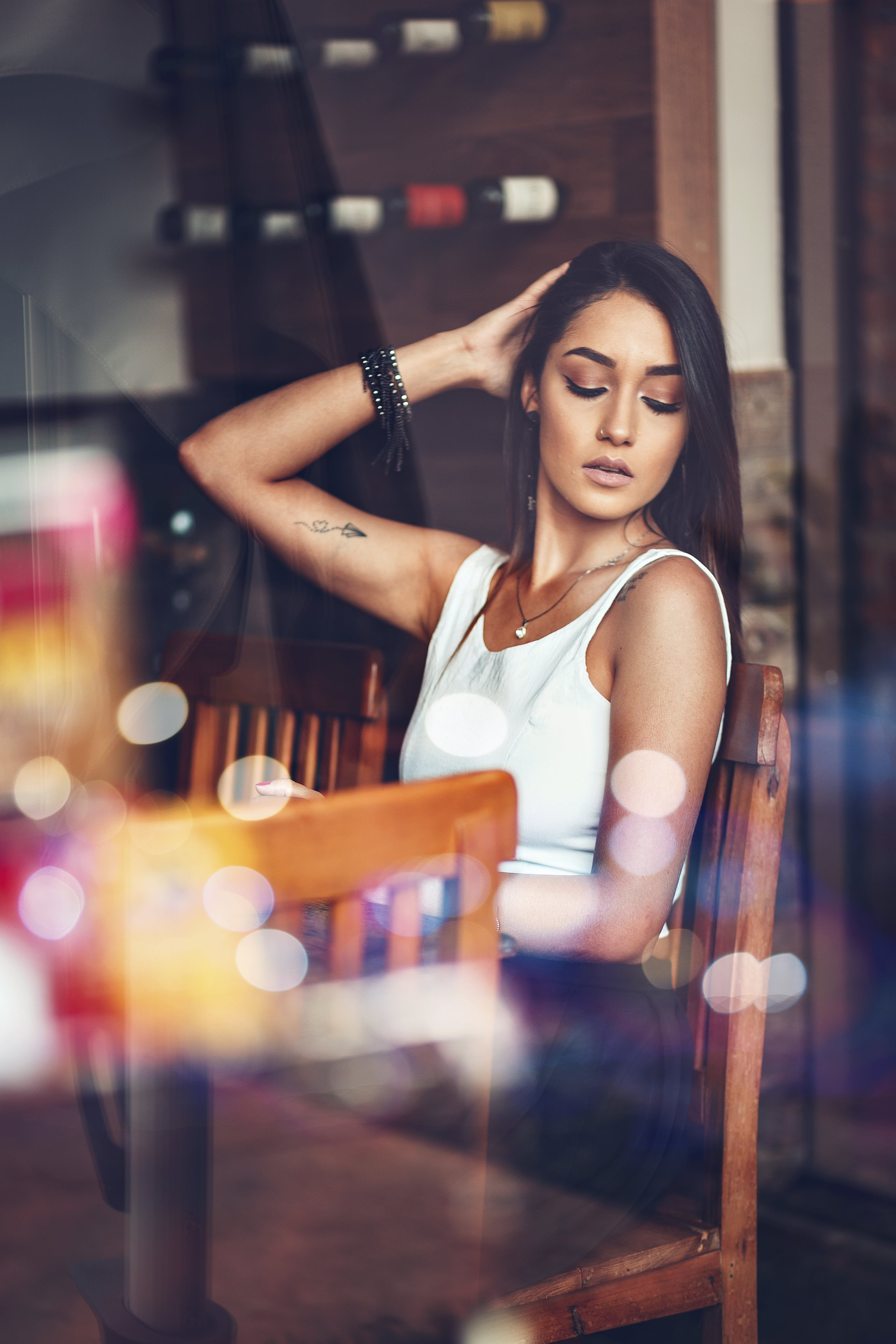 Woman in White Tank Top Sitting Beside Table