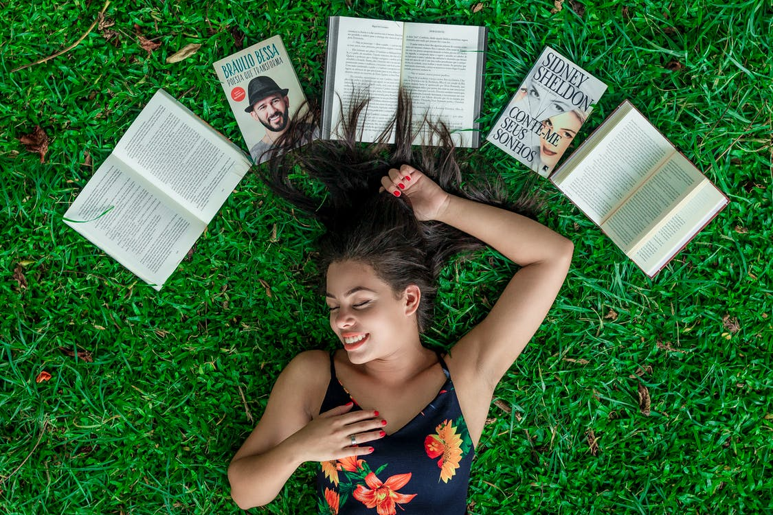 Woman Lying Down on Grass Beside Opened Books