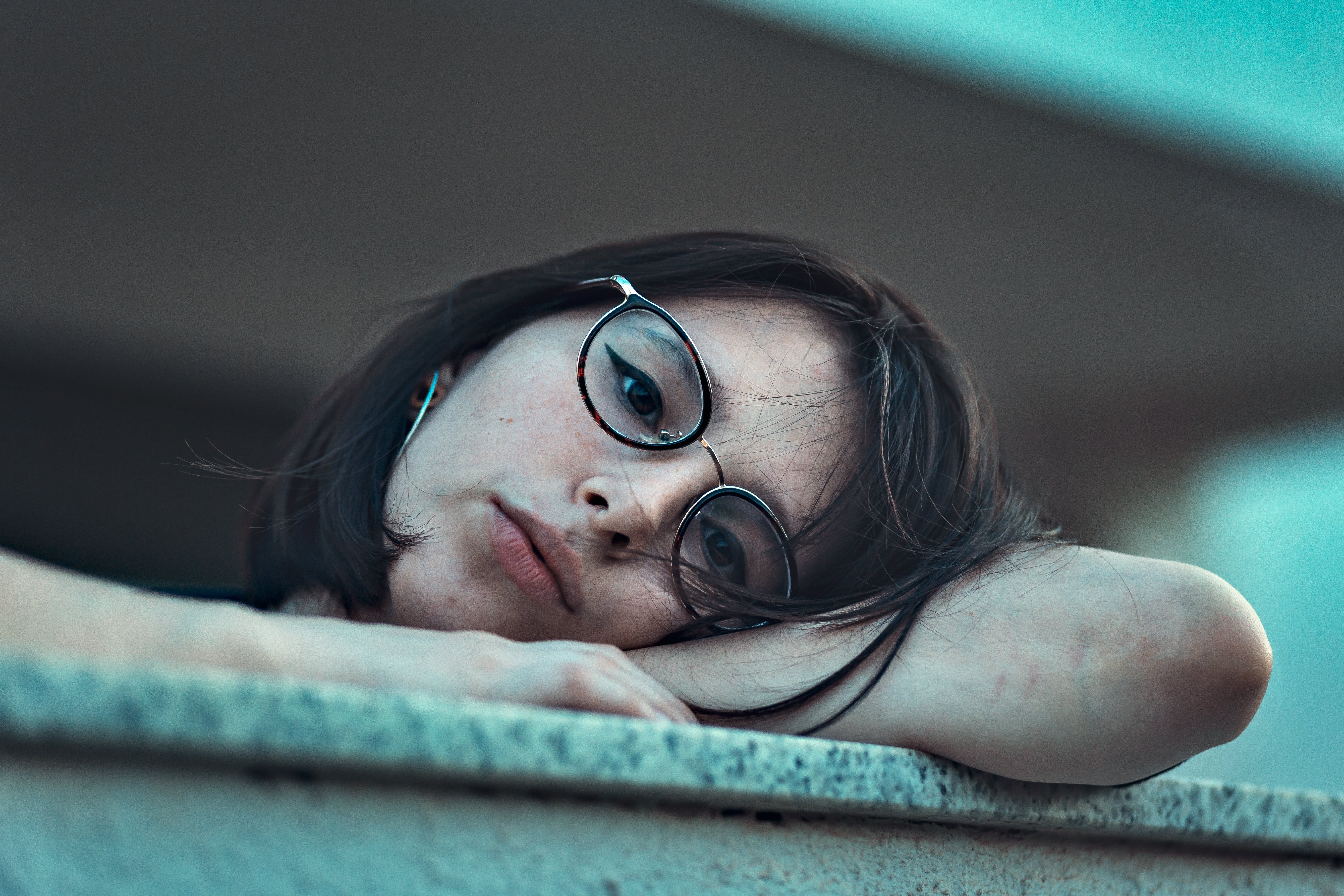 Photo of Woman in Eyeglasses Resting Her Head on Arm