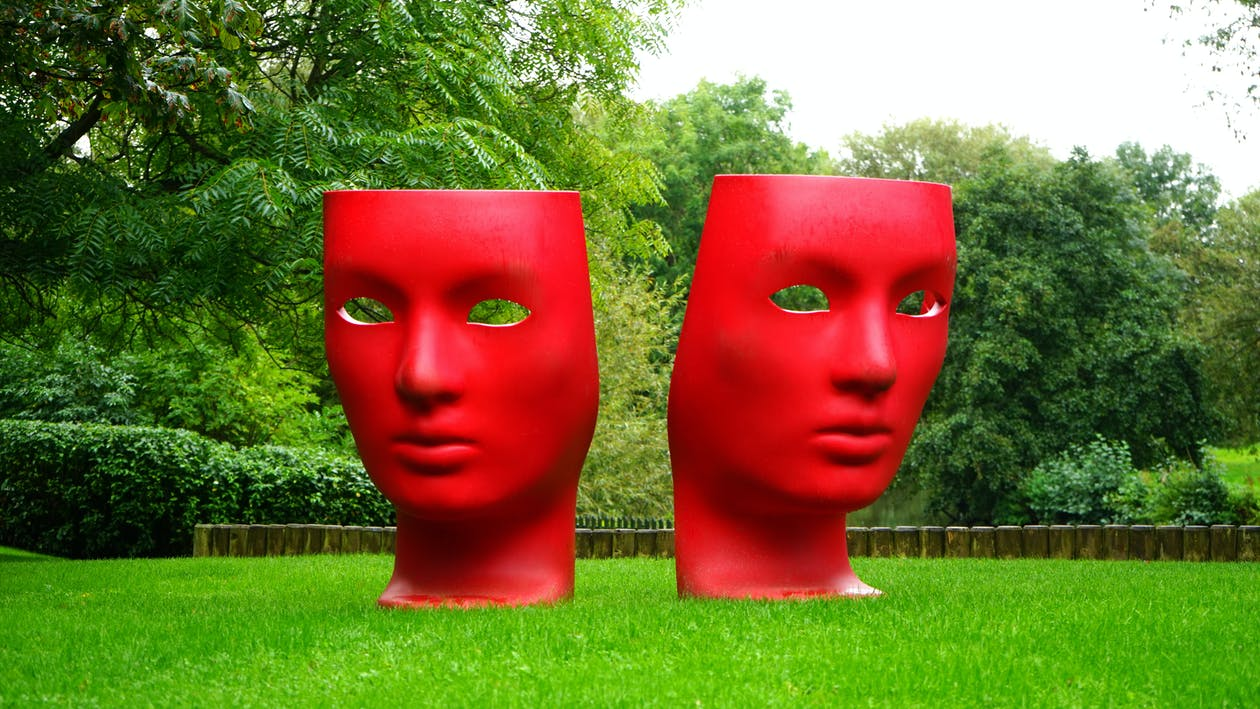 Red Human Face Monument on Green Grass Field