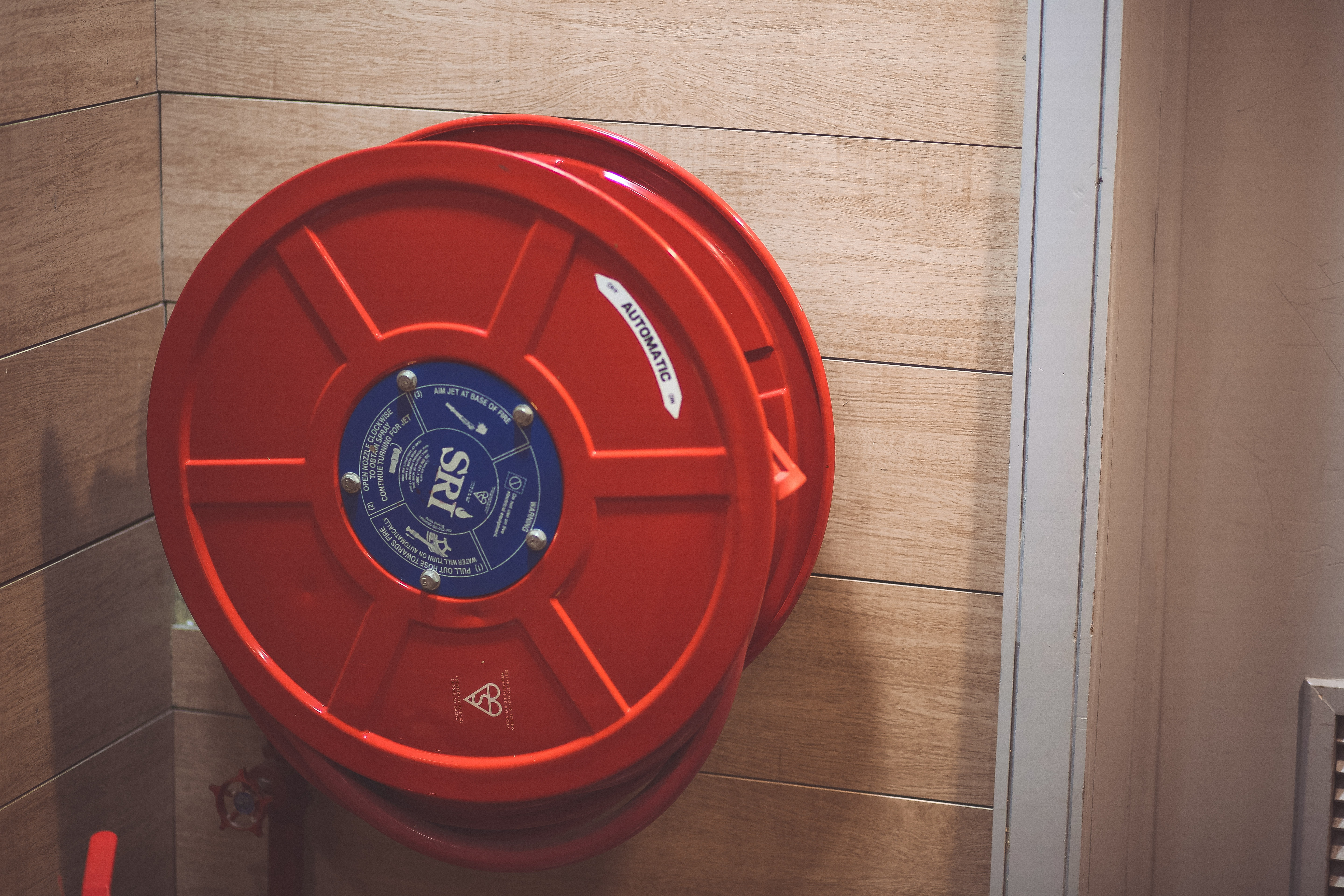 Red Hose Storage Handle & Red Fire Extinguisher Beside Hose Reel Inside the Room · Free Stock ...