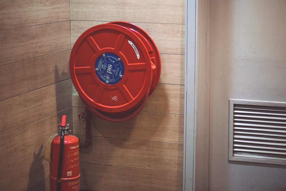 Red Fire Extinguisher Beside Hose Reel Inside the Room
