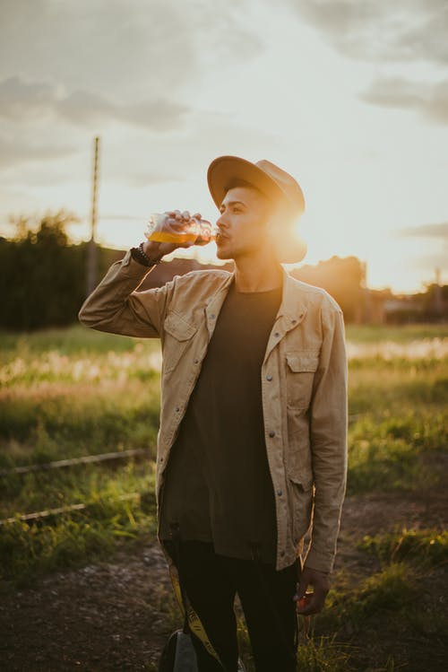 Photo of Man Drinking Juice Outside During Golden Hour