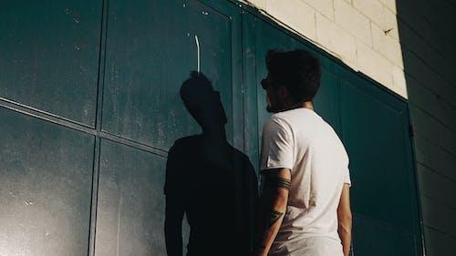 Základová fotografie zdarma na téma bílé tričko, brána, černá, muž