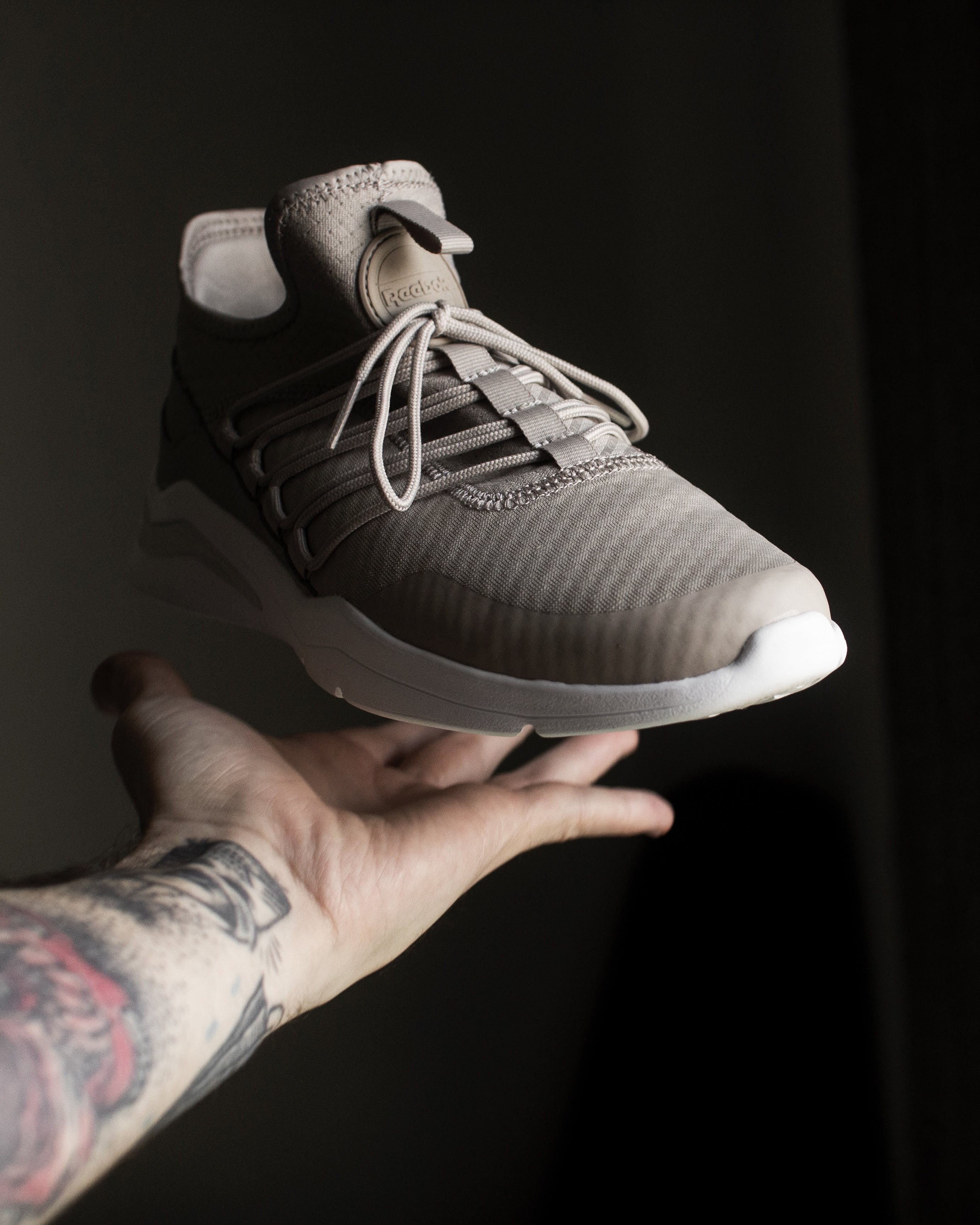 Gray and White Adidas Low-top Sneaker on Person's Fingers
