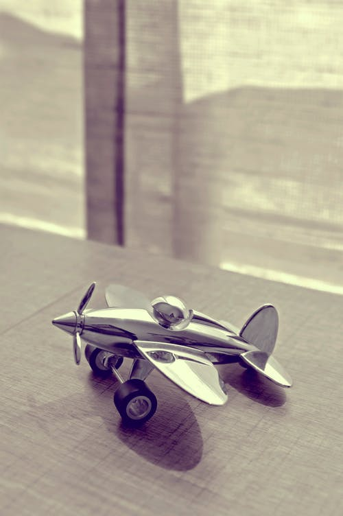 Sepia Photography of Stainless Steel Biplane on Brown Wooden Table Near Window during Daytime