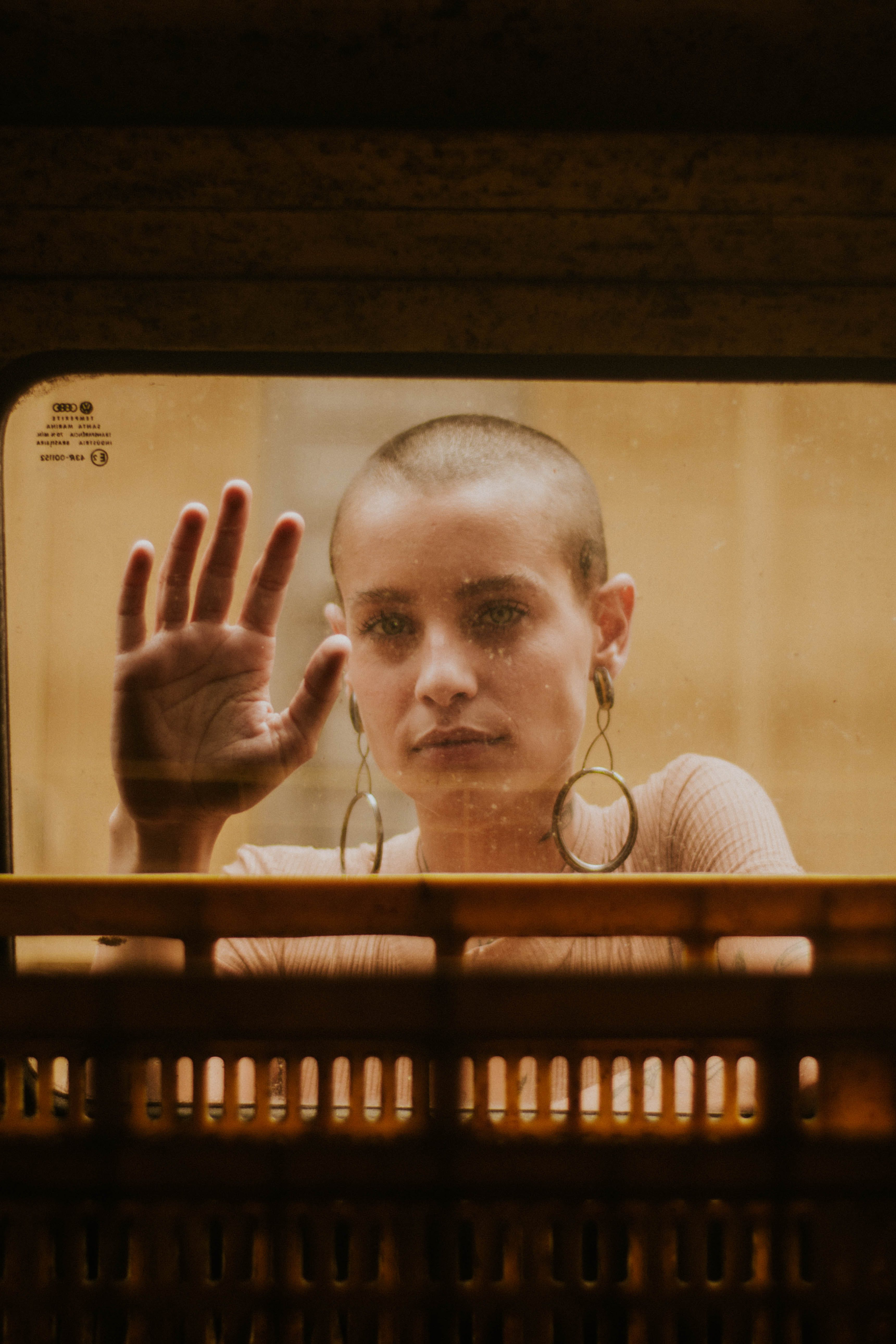 Bald Woman Touching Clear Glass Window